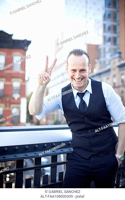 Businessman making a peace sign gesture, smiling cheerfully, portrait