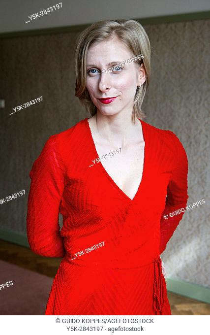 Tilburg, Netherlands. Young adult caucasian woman wearing a red dress standing inside a vintage room