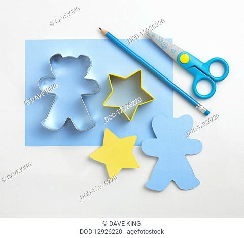 Cookie cutters, paper, pencil and scissors on white background, close-up