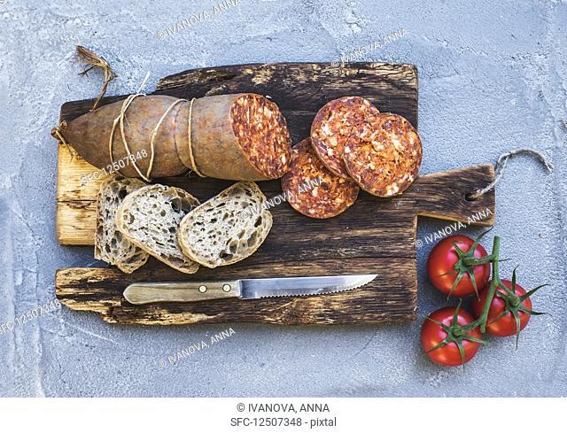 Wine snack set. Hungarian mangalica pork salami sausage, rustic bread and fresh tomatoes on dark wooden board
