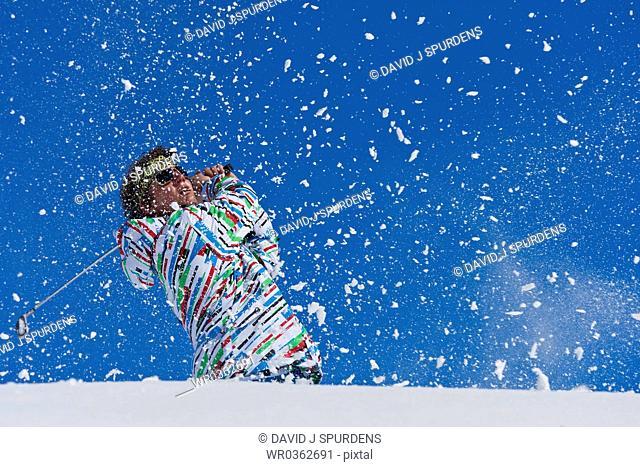 Golfer swings on snowy course
