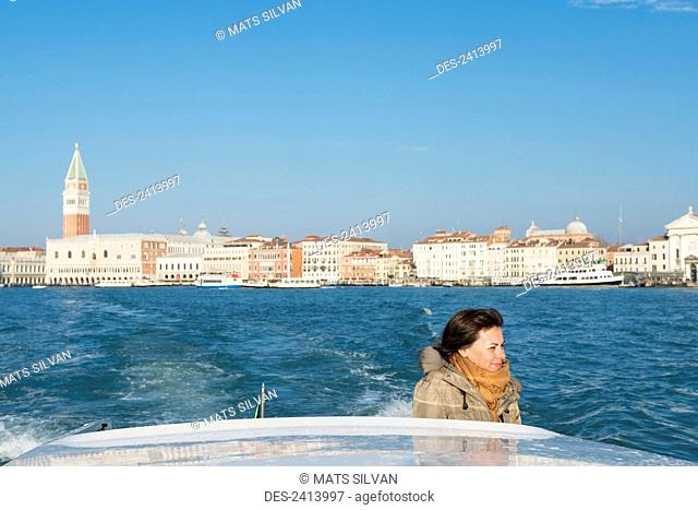 A woman stands on the back of a boat with a view of the shoreline of the Grand Canal in the distance; Venice, Veneto, Italy