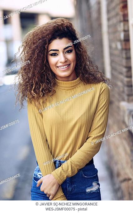 Portrait of smiling young woman with curly hair