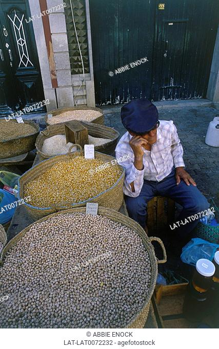 Man sitting by sacks of dried pulses/ beans in market