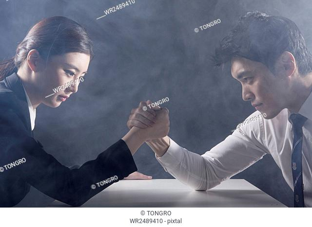 Side view portrait of businessman and businesswoman arm wrestling