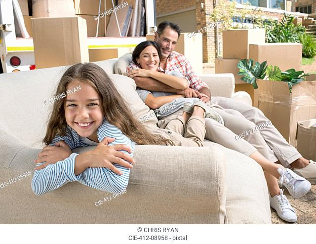 Portrait of smiling family on sofa in driveway near moving van