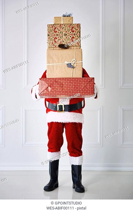 Santa Claus holding stack of Christmas presents