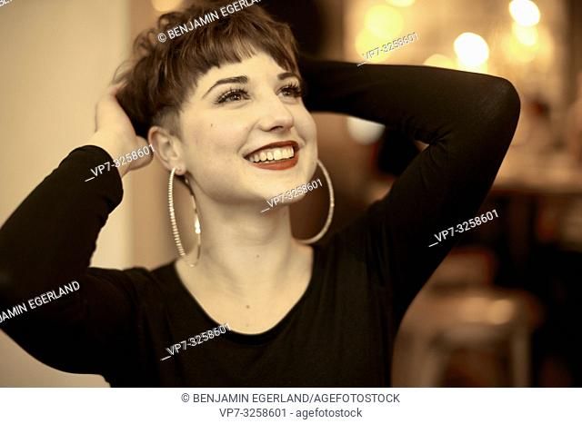 portrait of short-haired woman laughing indoors, in Cottbus, Brandenburg, Germany