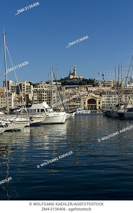 The Vieux Port (old port) with boats in Marseille, France with the Notre-Dame de la Garde (Our Lady of the Guard), a Catholic basilica in the background