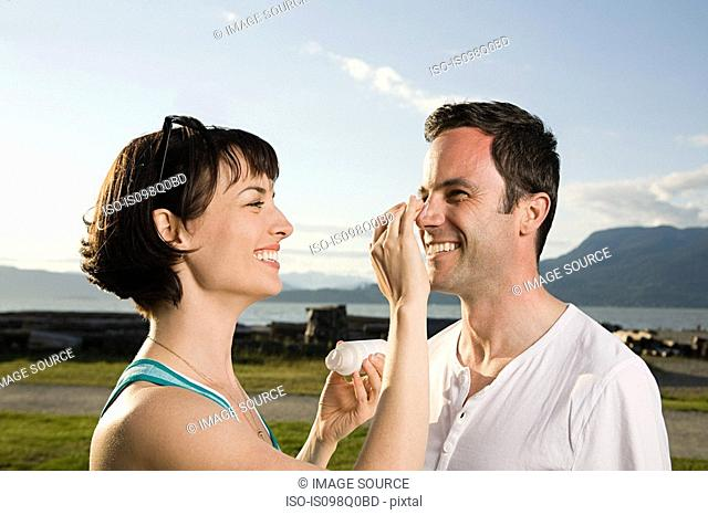 Couple applying suntan lotion