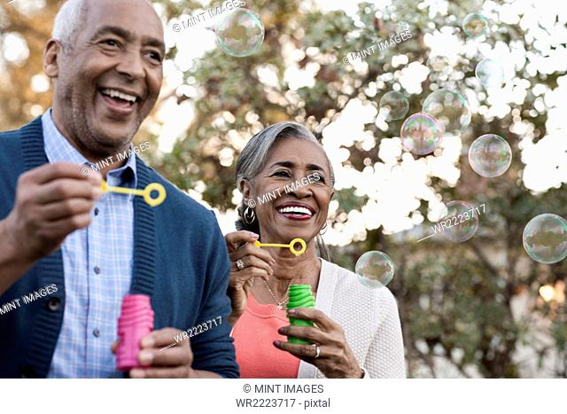 A mature couple, man and woman blowing bubbles celebrating an occasion outdoors