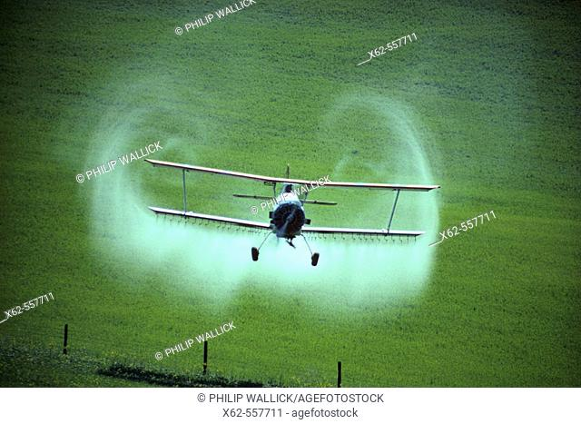 Crop duster spraying fields. California. USA