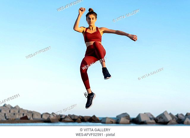 Sportive young woman during workout, jumping