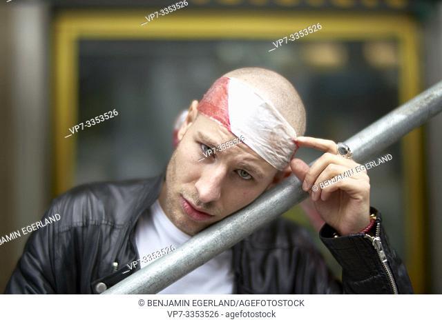 urban man wearing barrier tape as bandeau