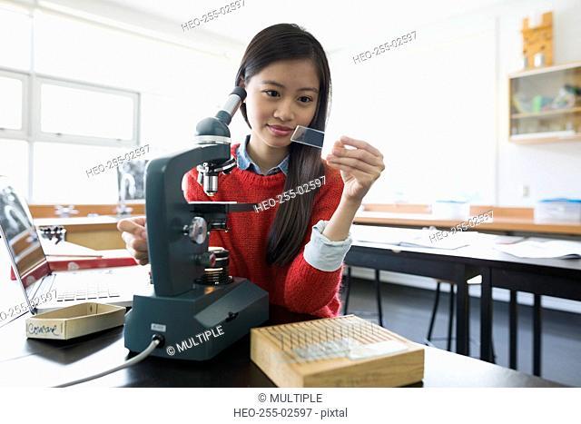 High school student examining microscope slide science laboratory