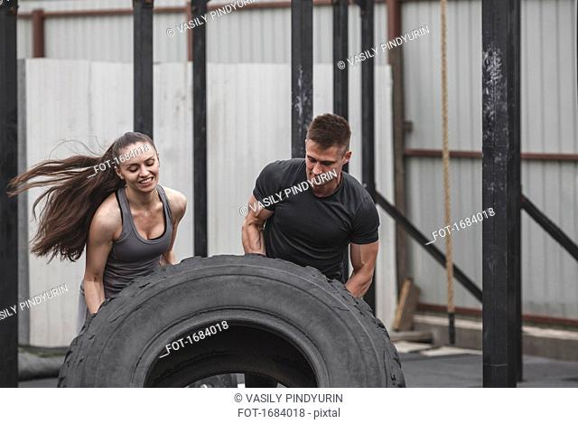 Male instructor assisting female athlete in flipping tire at gym
