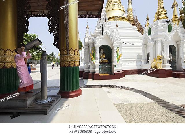 Child watches the decorations on the top of dome of the Pagoda with binoculars, Shwedagon pagoda, Yangon, Myanmar, Asia