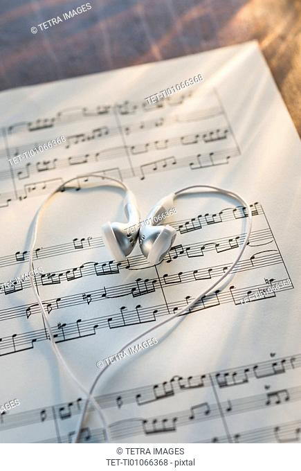 Studio shot of sheet music with earphones
