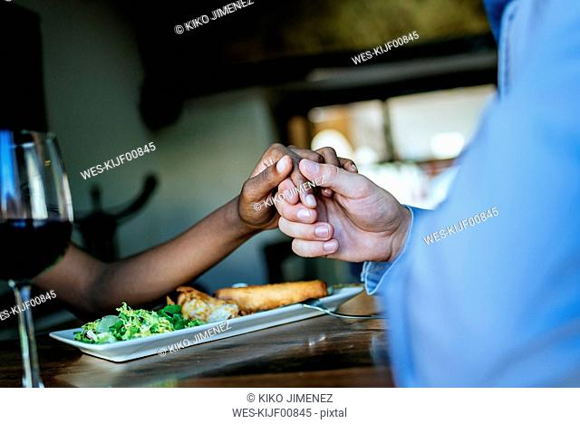 Close-up of a couple holding hands in restaurant