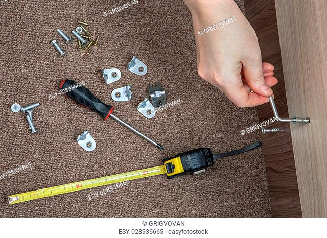 Assembling wood furniture used Hex wrench, Allen Key, human hand makes screwed furniture screw