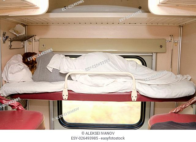 Passenger train sleeping on the top shelf of the side seats in the second-class carriage turned to the wall