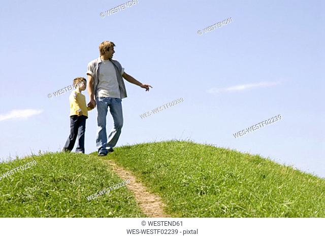 Father walking with son (4-7) hand in hand, low angle view