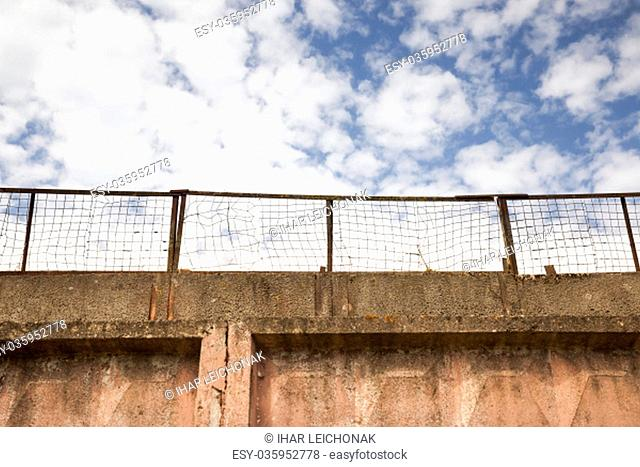 Part of the fence with a metal mesh on top. blue sky. The old part of the building and the fencing of the territory