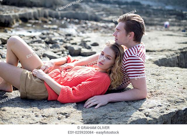Beautiful couple lying on a rock at the beach. They look very happy and content together