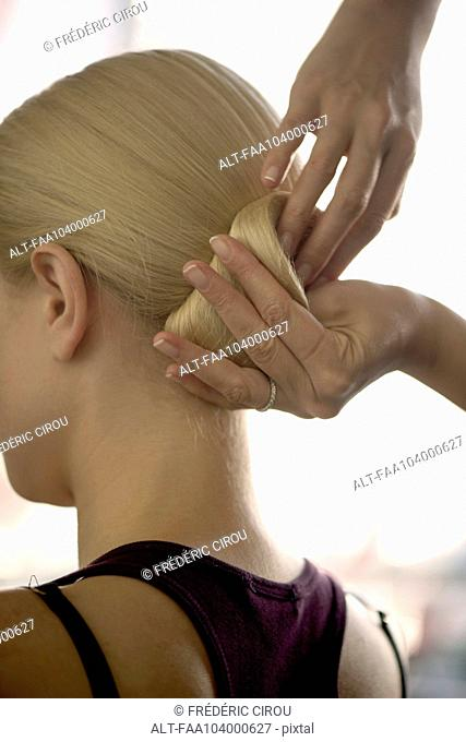 Hairdresser arranging woman's hair in a chignon, cropped
