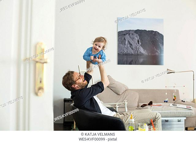 Father lifting up his daugther in living room