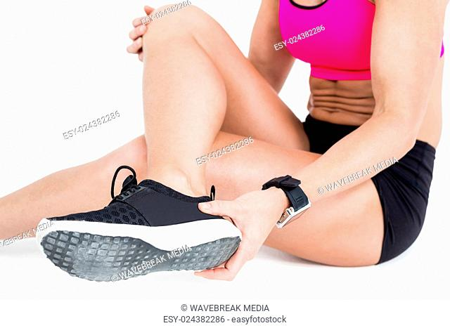 Injured female athlete sitting and removing her shoe