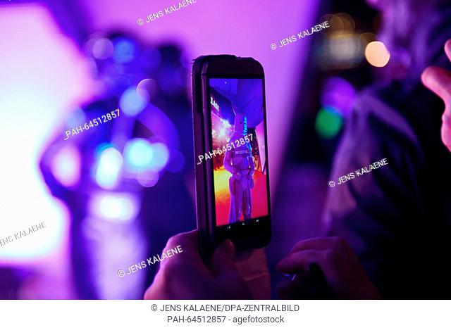 A guest at the premiere takes a picture of Star Wars characters with a smartphone at the German premiere of the new film 'Star Wars:The Force Awakens' in the...