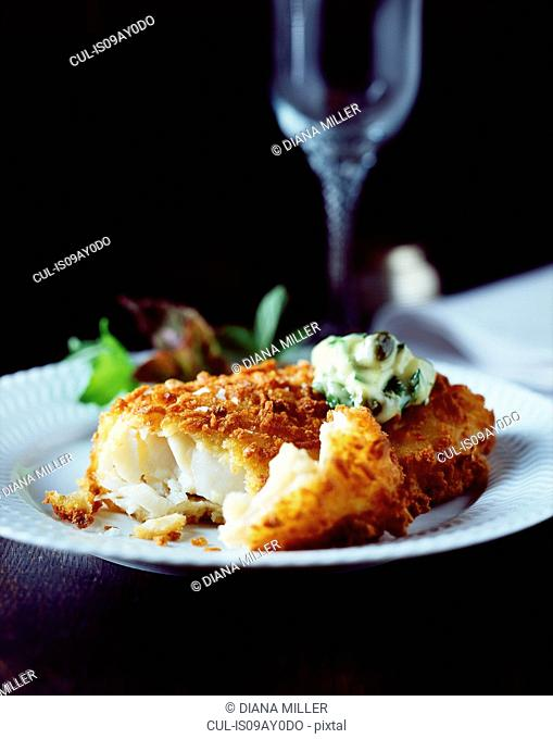 Breaded fish with creamy spinach sauce and salad on white plate
