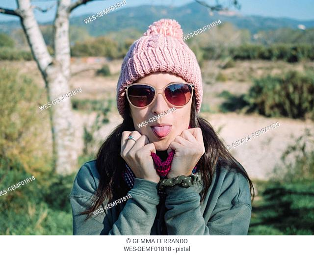 Happy woman sticking tongue out outdoors in winter with a wool hat and sunglasses