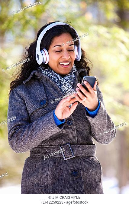 Young woman of South Asian ethnicity using cell phone and Bluetooth headphones in Scanlon Creek Conservation Area; Ontario, Canada