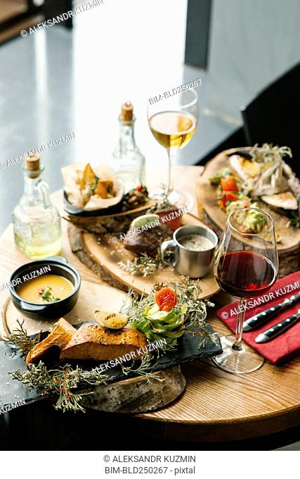 Variety of meat and fish on table with wine