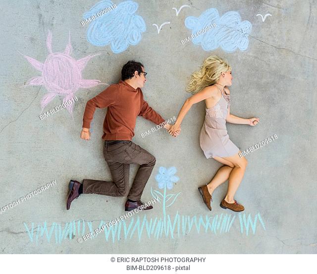 Caucasian couple posing over sidewalk chalk drawing