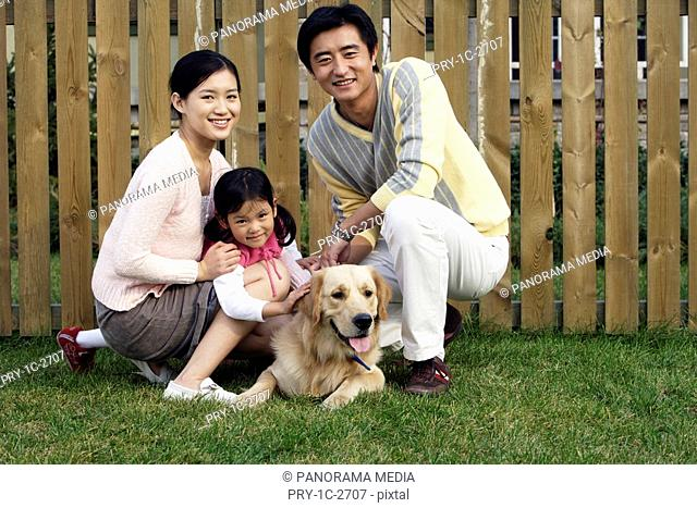 young family in front of the fense with their dog