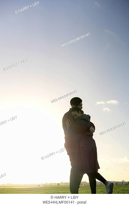 Affectionate young couple hugging on a meadow at sunset