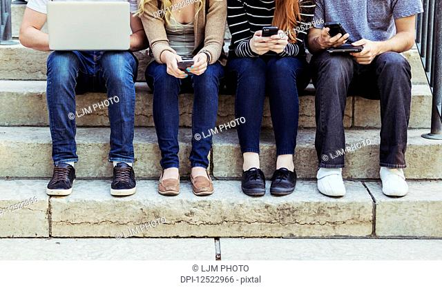Four students sitting in a row on a step using their technology on the university campus, with a view of their feet and legs only; Edmonton, Alberta, Canada