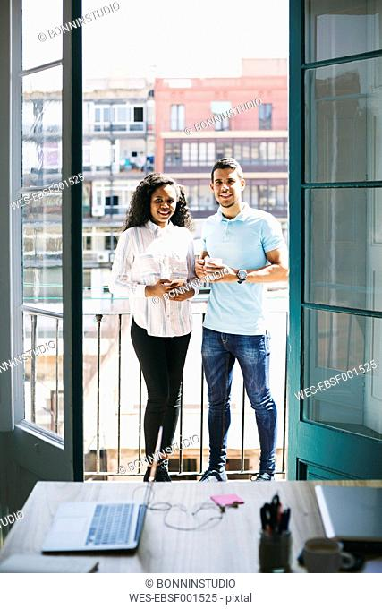 Two young business people standing on balcony with cup of coffee