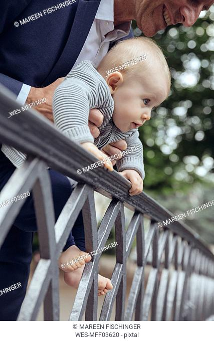 Father holding his baby to look over a fence