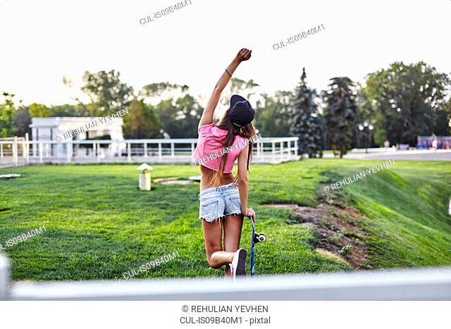 Young woman walking through park, carrying skateboard, punching air, rear view