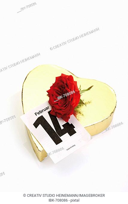 Golden heart-shaped gift box with a red rose and calendar page marking February 14th, Valentine's Day