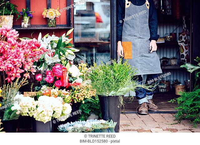 Caucasian florist standing in shop doorway