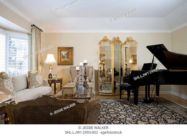 LIVING ROOM: grand piano, black floral pattern rug, folding mirrored screen, beige sofa and french style caned chairs