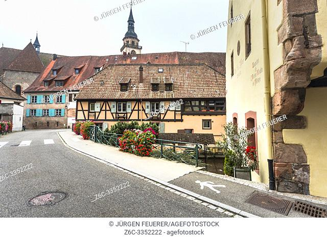 street of the village Andlau, Alsace Wine Route, France, half-timbered houses and ancient monastery with church in the background