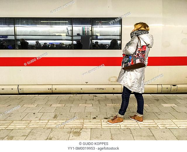 Utrecht, Netherlands. Caucasian female commuter waiting for her connecting train, while a German ICE is departing from the platform, bound for Berlin, Germany