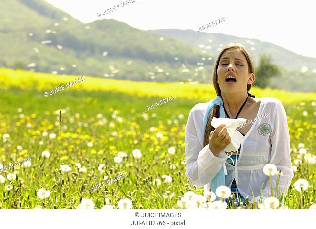 Woman sneezing with tissue in meadow