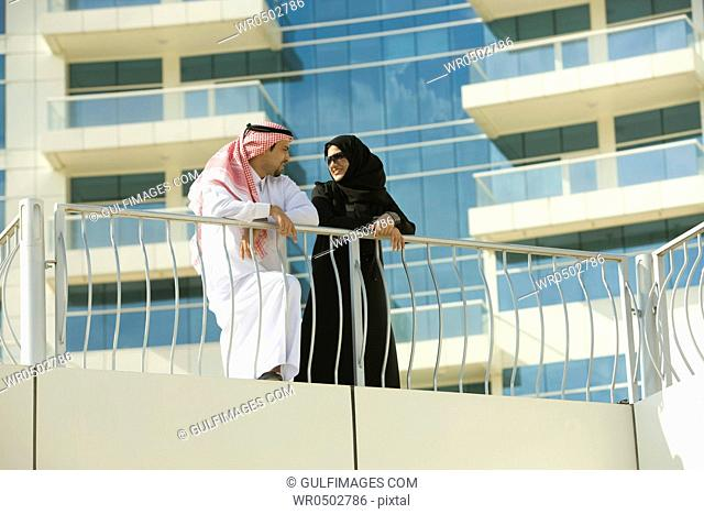 Arab couple standing by the railing of a building at Dubai, UAE
